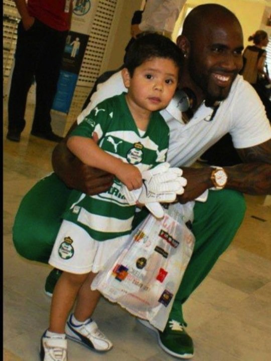 Santos Laguna player poses with small child and the Playboy magazine he just bought— SO