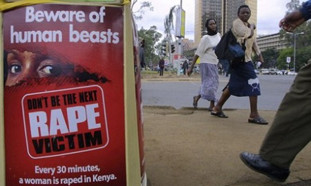 People walk past a poster bearing a message against rape on a street in Nairobi, Kenya. Photograph: Simon Maina/AFP/Getty