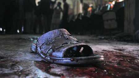 A bloodstained shoe of a victim lies on the ground at the site of a grenade attack on a crowded movie theatre. Source: AP