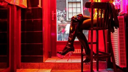 A-German-prostitute-called-Eve-waits-for-clients-behind-her-window-in-the-red-light-district-of-Amsterdam-AFP