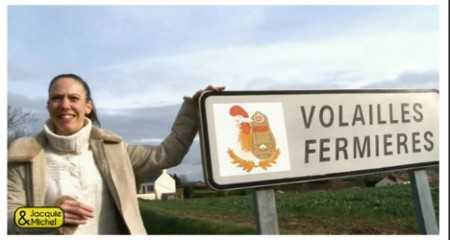 The video opens innocently enough with the woman posing near the roadside sign for the famous village,