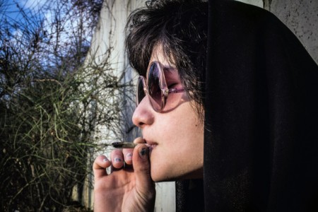 A young woman smokes marijuana on the hidden side of a park in Tehran in February, 2014. Photo: Barcroft