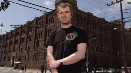 Peter Acworth stands in front of his studio and office complex, the former San Francisco National Guard Armory and Arsenal