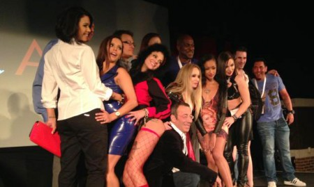 "Women In Porn: They Direct, Win Awards, Control Their Careers; More Progressive Than Hollywood? Pictured: ""Gonzo"" legend, director John Stagliano (kneeling) at an AVN party hosted by Evil Angel, with director/performer Dana Vespoli (far left) and Aiden Starr (middle). Other performers include Bonnie Rotten (in red) and Skin Diamond, to Starr's left. January 23, 2014.  PHOTO:  Barbara Herman"