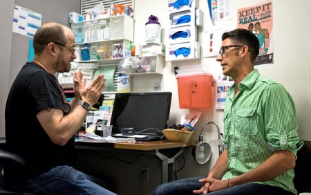 Pierre-Cedric Crouch, left, discussing with Jesse Eller the clinic's PrEP program, which uses medicine to prevent HIV infection.